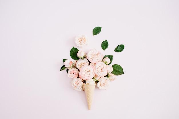 Waffelkegel mit rosa bombastischem rosenstrauß auf blassem pastellrosa hintergrund. flach legen