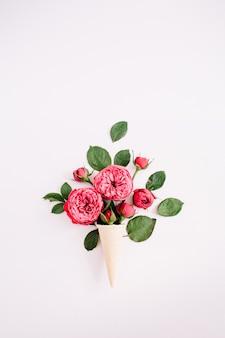 Waffelkegel mit rotem rosenstrauß auf hellem pastellrosa