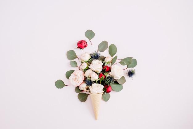 Waffelkegel mit roten, beigen rosen und eukalyptus-bouquet auf blassem pastellrosa hintergrund. flach legen