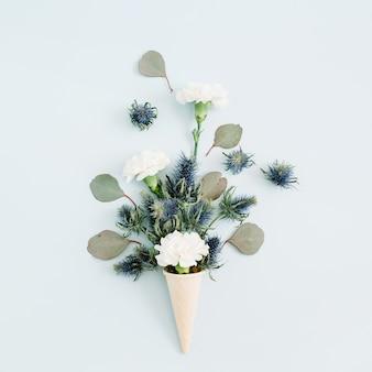 Waffelkegel mit weißer nelke und eukalyptus-bouquet auf hellpastellblauem hintergrund. flach legen