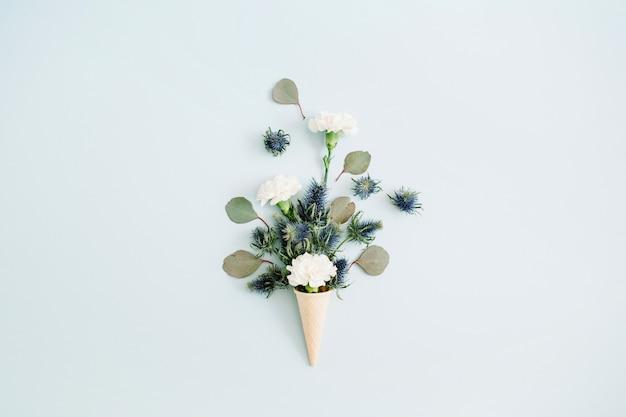 Waffelkegel mit weißer nelke und eukalyptusbouquet auf hellem pastellblau