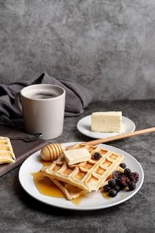 Waffeln auf teller mit honig und butter