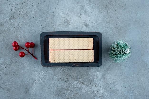 Waffeln in einem kleinen tablett neben weihnachtsschmuck auf marmoroberfläche