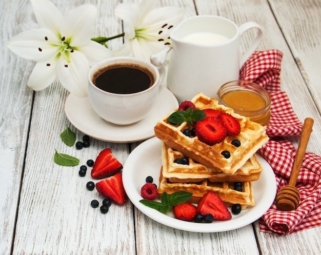 Waffeln mit erdbeeren, heidelbeeren und kaffee