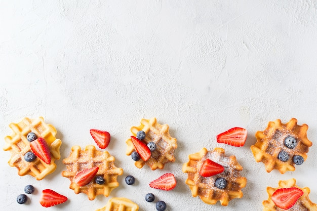 Waffeln mit erdbeeren und heidelbeeren grenze auf grauem hintergrund