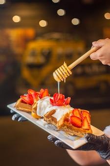 Waffeln mit erdbeeren und schlagsahne und honig auf weißem teller auf kellnerhand