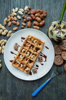 Waffeln mit nüssen und schokoladenmasse zum frühstück