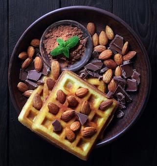 Waffeln mit schokolade und mandelnüssen draufsicht.