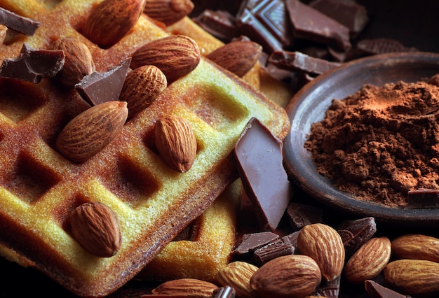 Waffeln mit schokolade und mandelnüssen nahaufnahme.