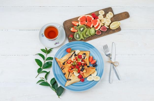 Waffeln und früchte in blauem teller mit früchten