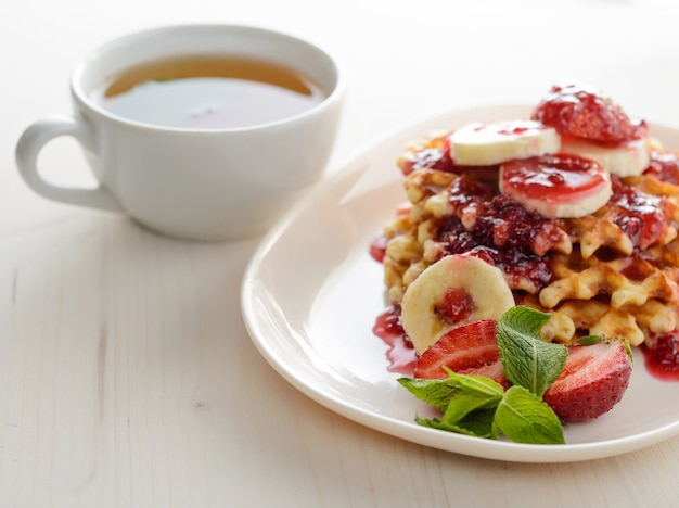 Waffelnachtisch mit erdbeerbananen und minze. tasse tee zum gesunden frühstück