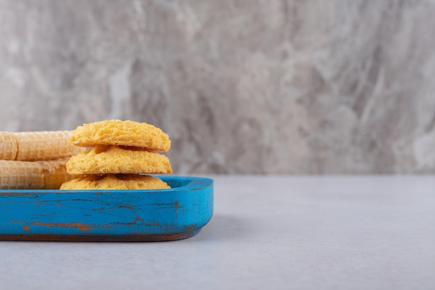 Waffelröllchen und kekse auf der holzplatte, dem marmor.