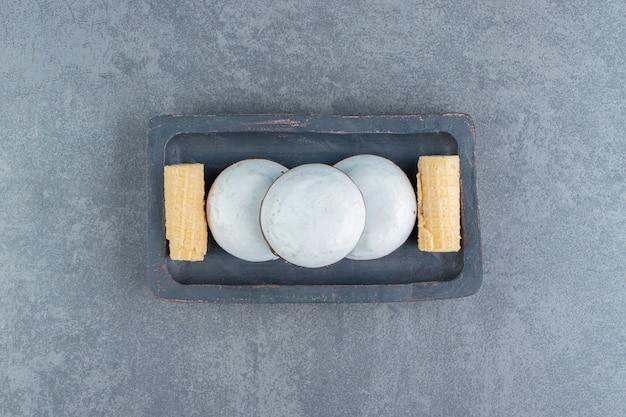 Waffelröllchen und kekse auf schwarzem teller.