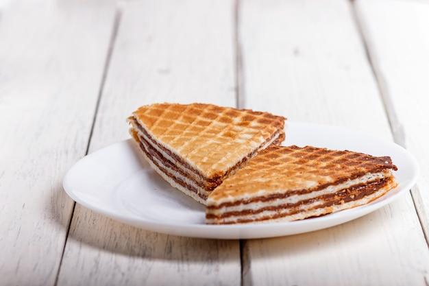 Waffelsandwiche mit gekochter kondensmilch in der platte auf weißem holztisch