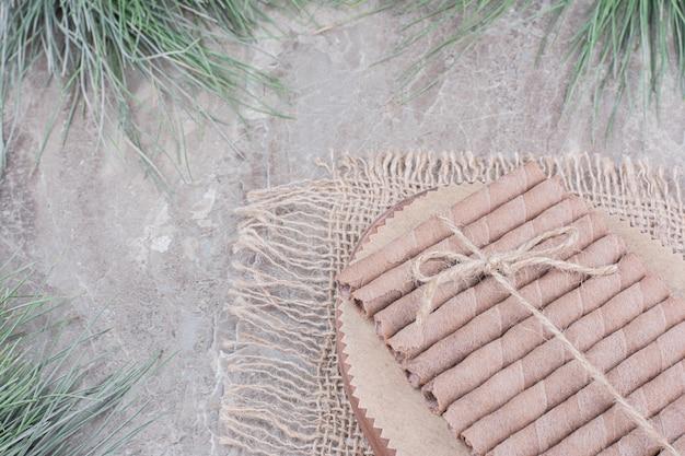 Waffelstangen mit einem faden auf einem holzbrett gewickelt