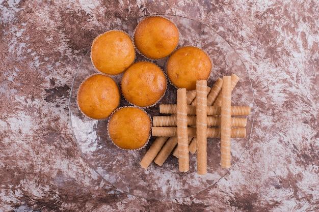 Waffelstangen und cupcakes in einer glasplatte auf dem marmor in der mitte