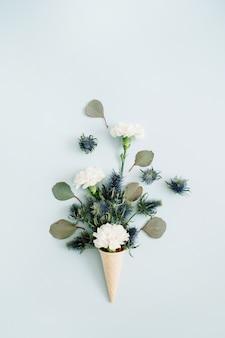Waffeltüte mit weißer nelke und eukalyptus-bouquet. flache lage, ansicht von oben