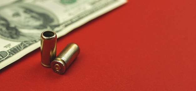Waffen und geld, kugel und dollar auf rotem hintergrund, kriminelles und illegales konzept, kopienraumfoto