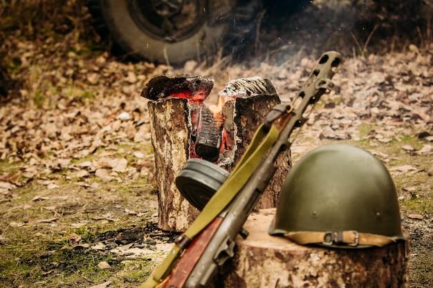 Waffen und sturzhelm der roten armee gegen den lagerfeuerhintergrund