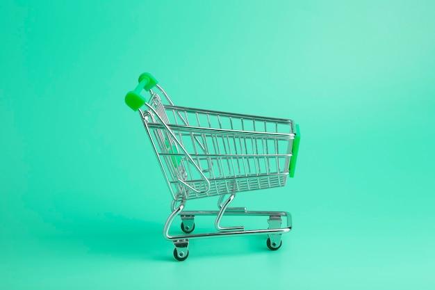 Wagen aus dem supermarkt minimal auf farbigem hintergrund. verkaufs- und einkaufskonzept.