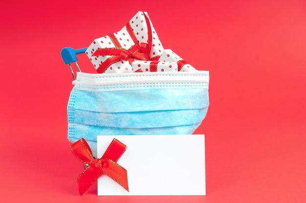 Wagen mit geschenken in schützender gesichtsmaske mit modell. geschenke für den urlaub während des virus kaufen