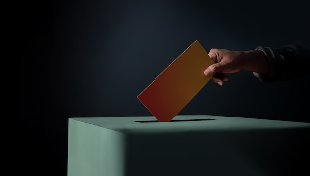 Wahlkonzept. person, die eine wahlkarte in die wahlurne fallen lässt, dunkler filmton