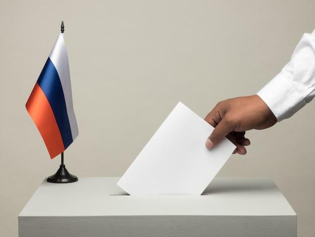 Wahlurne mit nationalflagge russlands. präsidentschaftswahl im jahr 2018. hand wirft einen stimmzettel