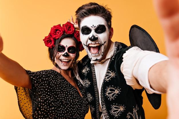 Wahnsinnige, lustige junge männer und frauen machen selfies und zeigen ihr skelett-make-up. mädchen mit blumen auf dem kopf und ihr freund haben spaß