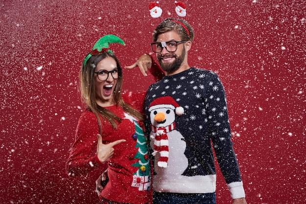 Wahnsinniges paar mit lustigen weihnachtsstrickjacken