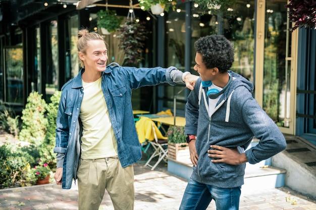 Wahre freundschaft. erfreuter blonder mann, der seinen besten freund ansieht, während er ihn begrüßt