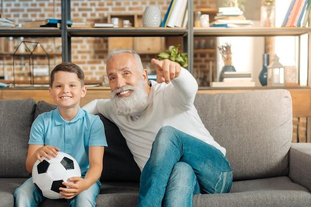 Wahre männer. glücklicher kleiner junge, der einen ball hält und ein fußballspiel im fernsehen zusammen mit seinem großvater sieht, der auf den bildschirm zeigt