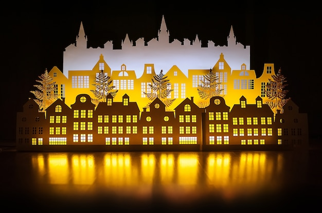 Wahre papierkunst nacht winter gold town mit neujahr lichter. fröhliche weihnachten.