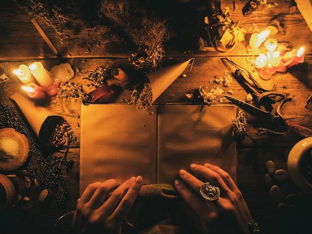Wahrsagen mit hilfe alter bücher und der trockenen afrikanischen kräuter. das licht der kerzen auf dem alten zaubertisch. attribute von okkultismus und magie.