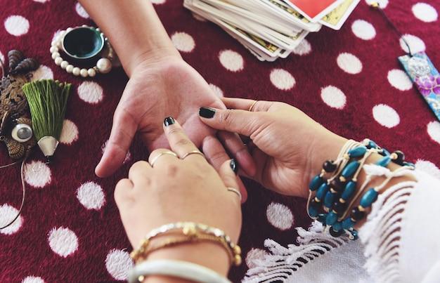 Wahrsagerin, die an hand vermögenslinien liest handlesen psychische lesungen und hellsehen übergibt konzept tarot-karten weissagung
