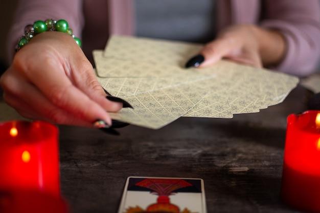Wahrsagerin liest eine zukunft durch tarotkarten auf rustikalem tisch