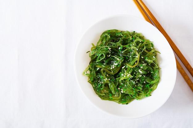 Wakame chuka oder algensalat mit sesam in schüssel auf weißem tisch. traditionelles japanisches essen. draufsicht. flach liegen