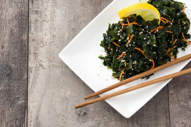 Wakame-salat mit karotte, samen des indischen sesams und zitronensaft in der platte auf holztisch