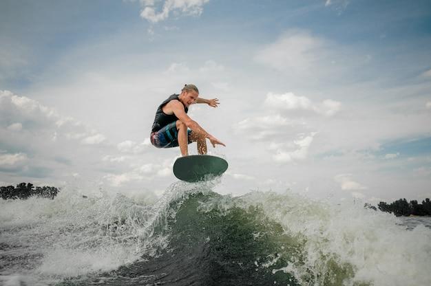 Wakesurf mitfahrer, der auf die wellen des flusses springt