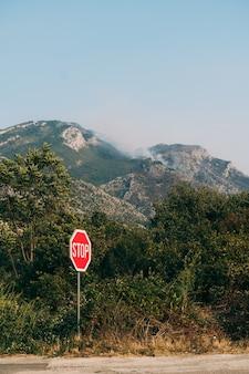 Waldbrand in den bergen und verkehrszeichen halten an