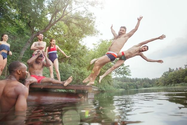 Waldparty mit freunden genießen. gruppe schöne glückliche junge männer und mädchen, die zusammen am fluss schwimmen. sommer, party, abenteuer, jugend, freundschaftskonzept Premium Fotos