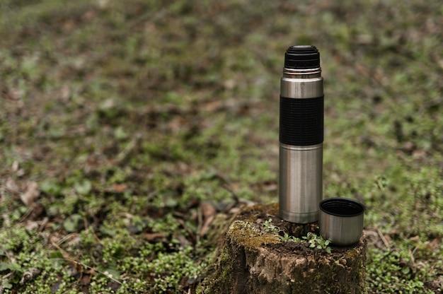 Waldwanderkonzept mit flasche auf baumstamm