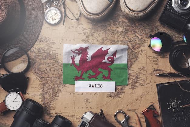 Wales-flagge zwischen dem zubehör des reisenden auf alter weinlese-karte. obenliegender schuss