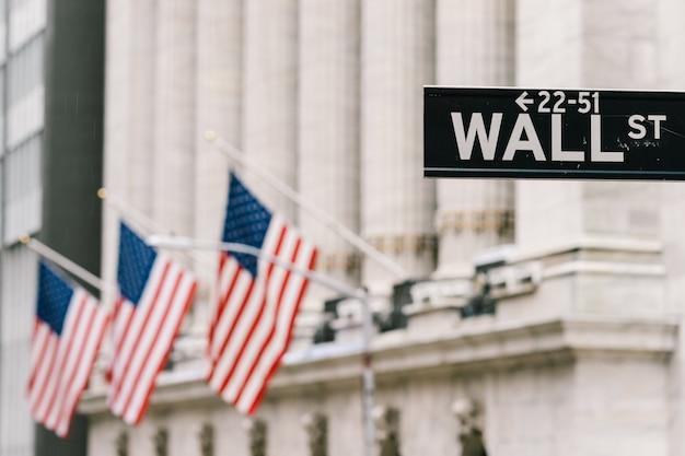Wall street-wegweiser mit amerikanischen staatsflaggen im hintergrund.