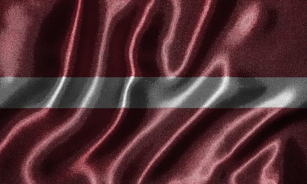 Wallpaper von lettland flagge und wehende flagge durch stoff.