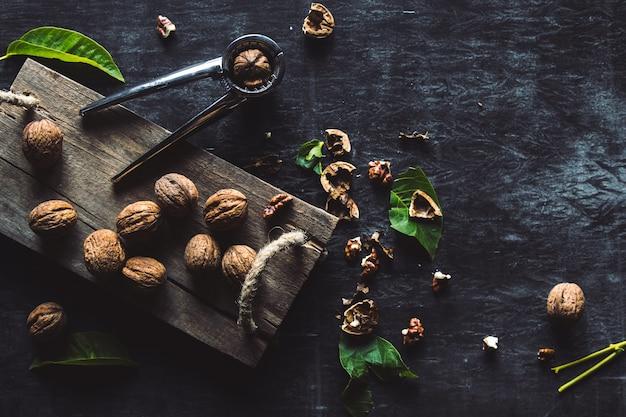 Walnüsse auf dunklem vintage tisch. gesundes essen. muttern sind auf einem schneidebrett verstreut. alter weinlese tisch und blätter von der nuss.