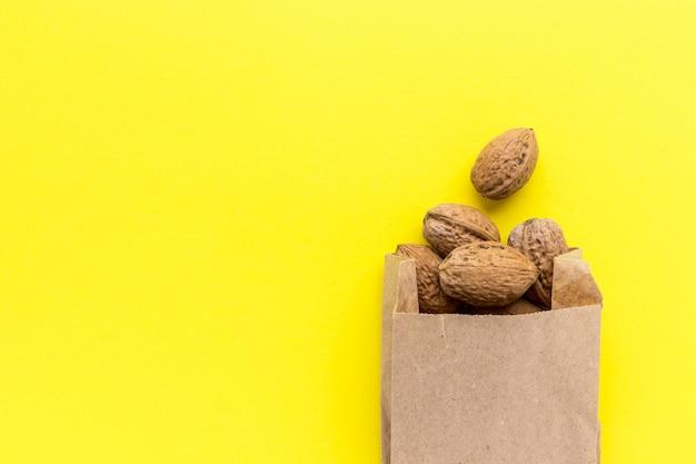 Walnüsse in der handwerklichen papiertüte auf gelbem hintergrund. leckere nüsse. gesunde ernährung. super essen. flache lage, draufsicht mit kopierraum.