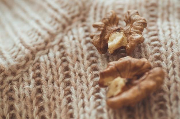 Walnüsse in pullovern. walnusskerne in einer schüssel und ganze walnüsse. gemütliches herbst- oder winterkonzept.