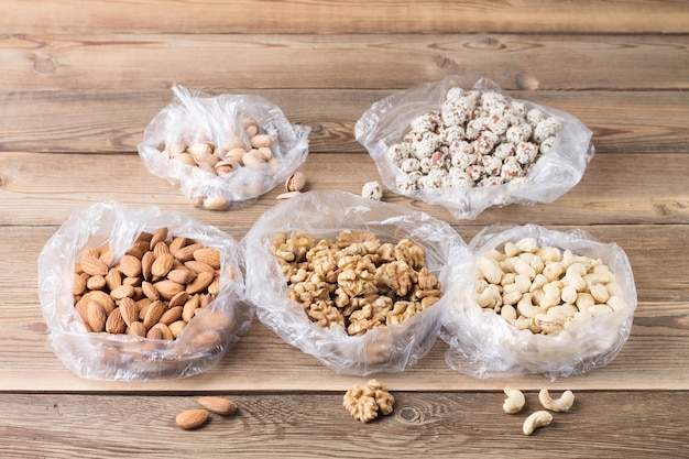 Walnüsse, mandeln, cashewnüsse, haselnüsse und pistazien in plastiktüten
