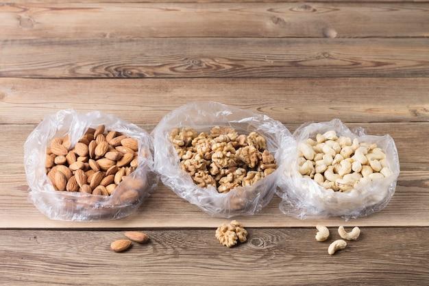 Walnüsse, mandeln, cashewnüsse in plastiktüten auf einem naturholztisch