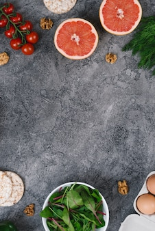 Walnüsse; traubenfrüchte; puffreiskuchen; spinat; eier und kirschtomaten auf grauem strukturiertem hintergrund